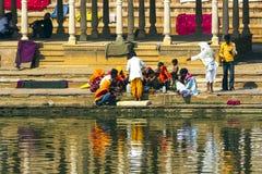 Peregrinos en un Ghat de baño en el lago santo Pushkar Imagen de archivo