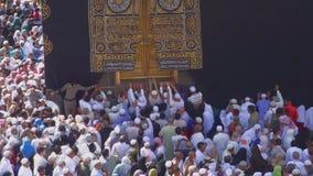 Peregrinos musulmanes que cuelgan sobre la puerta de Kaaba en Masjidil Haram en Makkah, la Arabia Saudita almacen de metraje de vídeo