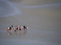 Peregrinos que cruzam a baía maré em Mont Saint Michel, França Fotos de Stock