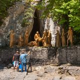 Peregrinos que iluminam velas antes da composição escultural do enterro do episódio do corpo de Jesus Christ após a crucificação, foto de stock royalty free