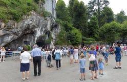 Peregrinos que visitan la cueva en Massabielle Foto de archivo libre de regalías
