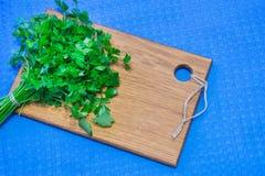 Perejil fresco en una tabla de cortar hecha de roble natural En la tabla de cocina con un mantel azul Lugar para su texto Foto de archivo