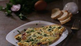 Perejil tajado fresco de extensión sobre la tortilla hecha de los huevos, tocino, queso metrajes