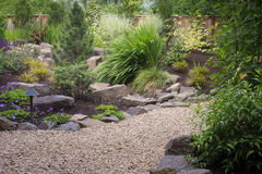 Perennials with rocks and path. A graceful pebbled walkway winds through this   perennial backyard garden Royalty Free Stock Photos