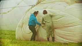 18-07-2019 pereslavl-Zalessky, Ρωσία: δύο άτομα που προετοιμάζουν τα μπαλόνια αέρα για να πετάξει και να λειάνει έξω το ύφασμα απόθεμα βίντεο