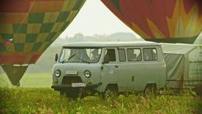 18-07-2019 Pereslavl-Zalessky, Rosja: samochód przyjeżdżał pole z ogromnymi kolorowymi lotniczymi balonami - zmierzch zbiory wideo