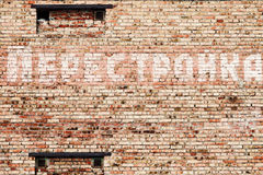 Perestroika slogan on the wall. Old faded Perestroika inscription on brick wall Stock Image