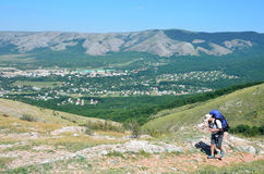 Perevalnoye, Crimea, July, 15, 2016. Man comes with a backpack on flat land along the Eastern cliffs of the lower plateau of. Perevalnoye, Crimea, man comes with royalty free stock image