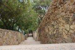 Perfeccione la pared al aire libre con las escaleras abajo de una colina entre una zona verde con el parque Fotografía de archivo libre de regalías
