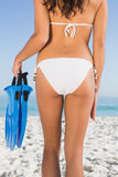 Perfeccione las nalgas femeninas de la mujer joven delgada que sostiene aletas Foto de archivo
