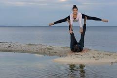 Perfect acroyoga. Beautiful young couple is doing yoga Stock Photos