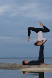 Perfect acroyoga. Beautiful young couple is doing yoga Stock Images