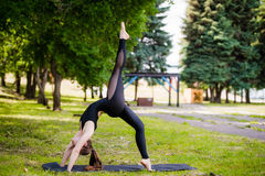 Perfect acroyoga. Beautiful young girl is balancing doing acro-yoga. Yoga flexibility outdoor class workout Royalty Free Stock Photography