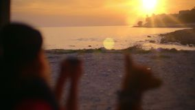 Young woman drink tea or coffee in van with dog. Perfect adventure and wanderlust broll inspirational and dreamy shot of sunset over beach, blurred young woman stock video footage