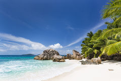Perfect Anse Patates, La Digue, Seychelles. Perfect white beach Anse Patates in La Digue, Seychelles with clear water, granite rocks, palm trees and deep blue Stock Image
