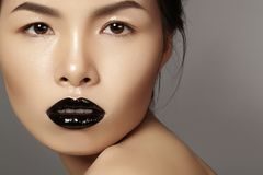 Close-up portrait asian model with fashion lips make-up, clean skin. Beauty halloween style with black lipstick makeup Royalty Free Stock Photo