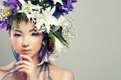 Perfect Asian Model Woman with Vivid Flowers and Fashion Makeup. Summer Fashion Girl with White Lily and Iris Flowers Royalty Free Stock Photography