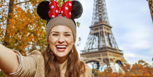 Tourist woman wearing Minnie Mouse Ears taking selfie in Paris. Perfect autumn holidays in Disneyland and Paris. happy tourist woman wearing Minnie Mouse Ears stock photos