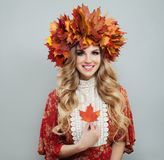 Perfect autumn woman in bright fall leaves crown holding red maple leaf.  stock photos
