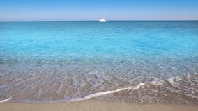 Perfect beach with sailboat in turquoise aqua color and the waves