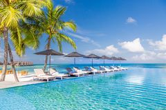 Perfect beach scenery with coconut palm tree around swimming pool in hotel and resort at sunny weather royalty free stock photos