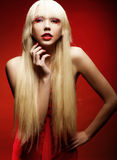 Perfect blond model in red dress over red background. Royalty Free Stock Photography