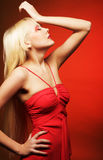 Perfect blond model in red dress over red background. Royalty Free Stock Image
