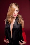Perfect blonde in a black dress on red Royalty Free Stock Image