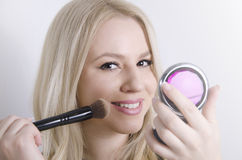 Perfect blonde Caucasian girl putting on makeup Stock Images
