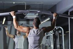 With Perfect Body modelo masculino muscular considerável que faz a tração levanta imagem de stock