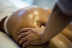 Perfect body. The masseur makes Anti-cellulite massage on the buttock and thighs of the patient. Close up stock photo