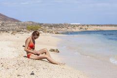 Perfect body sexy redhead model in orange bikini holding sand sitting near water on papagayo beach. Lanzarote, Canary Islands, Spa. Lady on Papagayo beach Stock Photos