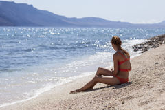 Perfect body sexy redhead model in orange bikini sit near water on papagayo beach. Lanzarote, Canary Islands, Spain Royalty Free Stock Photos