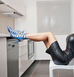Perfect body woman in short tight fit leather dress and blue shoes posing relaxed in a modern kitchen. Side view of sensual girl Stock Image