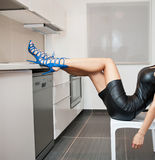Perfect body woman in short tight fit leather dress and blue shoes posing relaxed in a modern kitchen. Side view of sensual girl Royalty Free Stock Photos