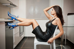 Perfect body woman in short tight fit leather dress and blue shoes posing relaxed in a modern kitchen. Side view of sensual woman Royalty Free Stock Photos