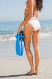 Perfect body of young woman holding fins Royalty Free Stock Image