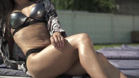 Perfect body of a young woman in silver swimming suit lying on a sunbed and sunbathing. Leisure of beautiful lady. Perfect body of a young woman in silver stock video