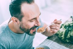 Hungry attractive man eating cereals for breakfast royalty free stock image