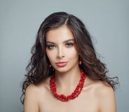 Perfect brunette model woman with makeup, long curly hair and red coral necklace.  stock photography