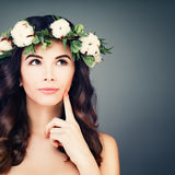 Perfect Brunette Woman with Healthy Skin. And Hair Looking Up. Flowers Wreath, Spring Makeup, Curly Hairstyle on Blue Background. Young Spa Model with Wavy Hair Stock Photos