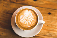 Perfect cappuccino in white cup on wood table Royalty Free Stock Photos