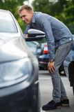 Perfect car for perfect man. Blur green backround. Handsome man choosing used auto. Looking at the details Royalty Free Stock Photos