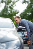 Perfect car for perfect man. Blur green backround. Handsome man choosing used auto. Looking at the details Stock Photography