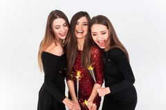 Perfect celebration night concept. Beautiful young women looking at camera and holding sparkler with smile while stock images