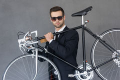 Perfect city transportation. Confident young businessman carrying his bicycle on shoulder while standing against grey background Stock Photo