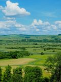 Perfect Clouds over Fields of British Farms. Perfect clouds in a blue sky over vast green fields in the British countryside near Arundel in West Sussex royalty free stock image