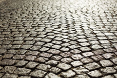 Perfect cobblestone streets of the city. Paving stone roadbed made with small stone blocks royalty free stock photo