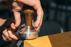 The perfect coffee that suits to your taste. Barista press coffee with tamper in portafilter. Brewing coffee equipment. Barista brew espresso drink in cafe royalty free stock image