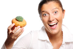 Perfect compromise. A picture of a young woman finding perfect compromise between eating a donut and broccoli Stock Photo